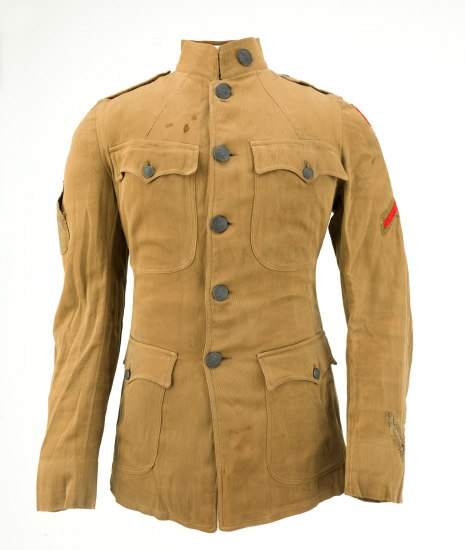 Photo of uniform jacket. It is light brown with buttons, four pockets, and fairly high, stiff collar. It isn't brand new but appears slightly aged.