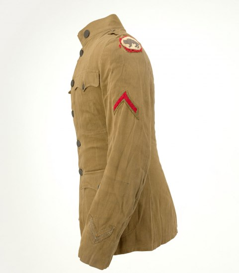 Side view, from which a buffalo patch lined in red is visible on upper shoulder. Photo of uniform jacket. It is light brown with buttons, four pockets, and fairly high, stiff collar. It isn't brand new but appears slightly aged.