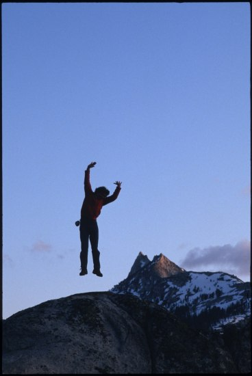 Photo of man (mostly silhouette) leaping into the air, arms raised, with a mountain peak in background. Snow visible on peak.