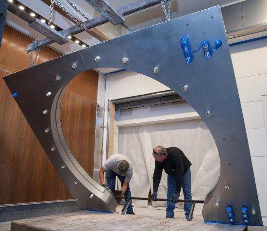 two men adjust base of square vault door which is being suspended by chains