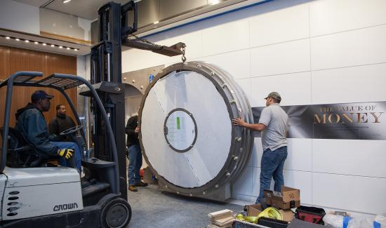 Two men line up the round door with the frame while it is suspended by a forklift