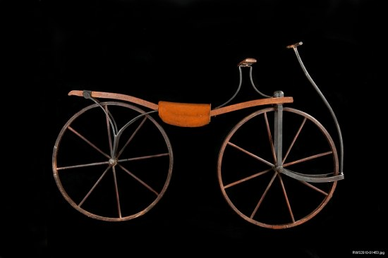 An old bicycle that has a single piece of wood as the body of the bicycle. It has two wooden, large-spoked wheels, what looks like a leather seat rest, and dark metal that attaches the bike together and forms a long handle or rod that is attached by the front wheel but extends to the height of the rider's hands