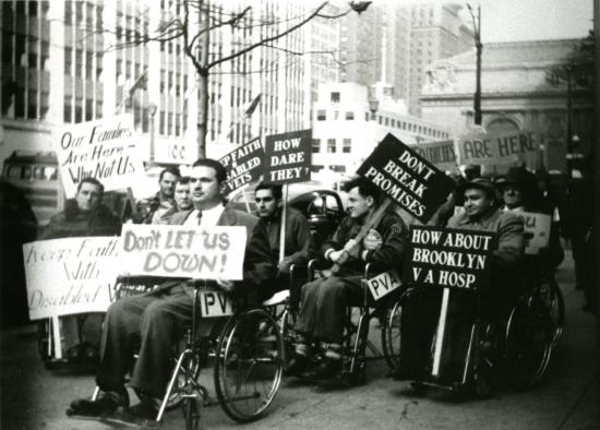 "Black and white photo of men in wheelchairs with signs that say ""Don't let us down"" ""How dare they?"" ""Don't break promises"" ""How about Brooklyn VA Hosp"" ""Our Families are here--why not us"" on sidewalk with buildings and trees in background."