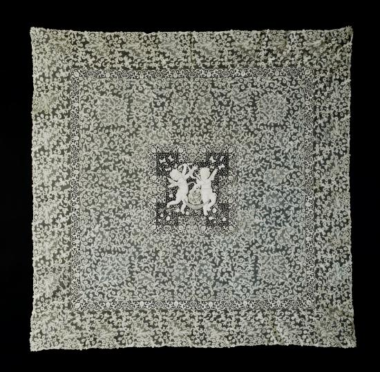 Square piece of lace. White on black background. Cherub in center.
