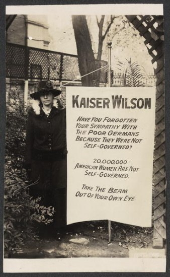 "Black and white photo. Woman wearing a wide-brim hat and coat stands beside large banner that says ""Kaiser Wilson..."""