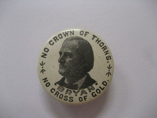 "A white campaign button that has a portrait of a man looking to the viewer's left on it with ""Bryan"" underneath. Around the edges reads: ""No crown of thorns. / No cross of gold."""