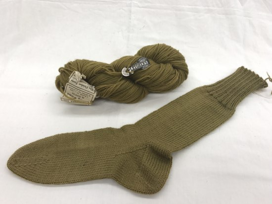 Photo of an Army green sock (with prominent ankle) and yarn knot.