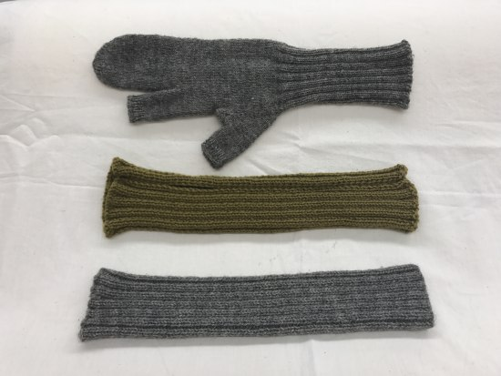 Three knitted items in Army green and grey. One is mitten-shaped. Two are tube-shaped.