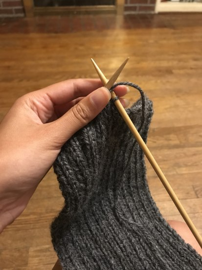 Photo of a person's hand knitting a gray wristlet