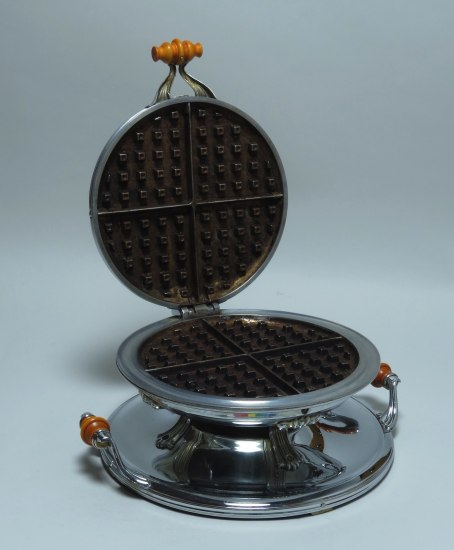 Waffle iron, silver in color. Open as though you're about to pour in some batter.