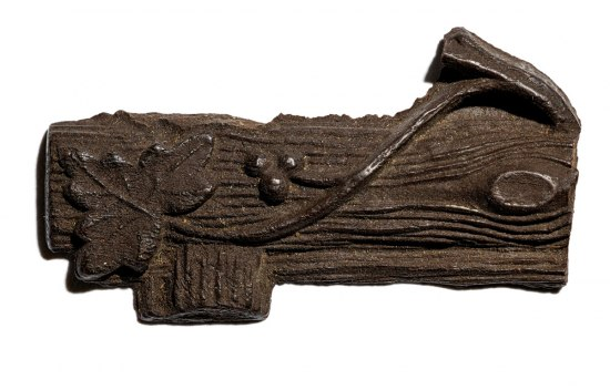 Fragment of wood with detailed carving of a leaf, vine, berries