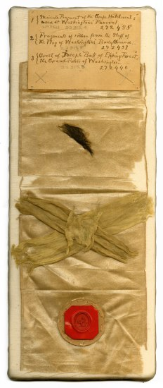 White ribbon with three items pasted to it: a piece of black crepe, a yellow silk ribbon, and a red wax impression of a crest. A handwritten note at the top identifies the items.