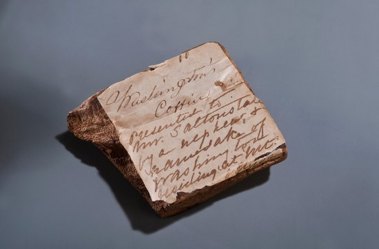 Piece of wood obscured by handwritten note of identification