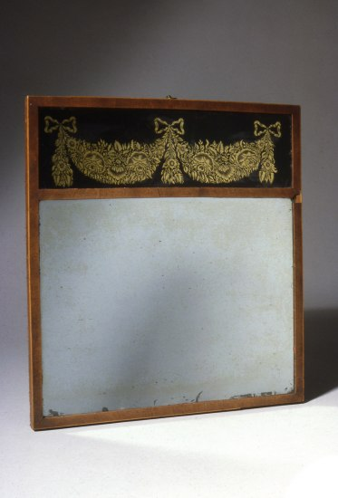Weathered rectangular mirror topped with a black and gold flower design.