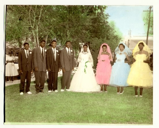 Tinted black and white photo featuring a bride with veil, three or four groomsmen, and three bridesmaids. They are outdoors with leafy green trees and green grass. Behind them, a woman stands with arms crossed and cars are parked.