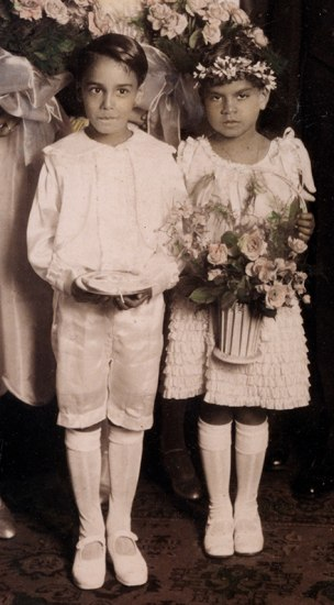 In a hand-tinted black-and-white photo, two children stand side-by-side as part of a wedding party.