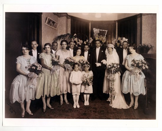 A grou of 13 adults and 2 children. Bride and groom with wedding party in formal dress. Women and flower girl hold bouquets. Each of the five bridesmaids wears a sparkly headband on her forehead. Their hair is short and coiffed. Behind the group, wooden doors, high ceilings, and oriental carpet.