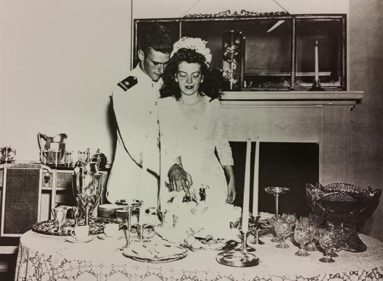 Just-married couple cuts a cake. He's in uniform, she's wearing a veil. Candle sticks and glass punch bowl on table.