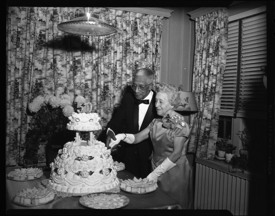 "Standing in front of a patterned curtain, a couple stands by a table. She's in a formal dress with brooch, pears, and white gloves. He's in a suit, bow tie, and glasses. They are an older couple. Together, they cut a multi-tiered cake with the number ""50"" on top. On the table, cake and cookies are displayed on five plates. There is a large bouquet of flowers."