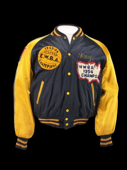 "A navy athletic letterman jacket with gold sleeves. There is a patch on the right breast with a basketball on it and a patch shaped like the U.S. with ""NWBA 1954 Champs."" The jacket has ""Ray"" above the America patch."