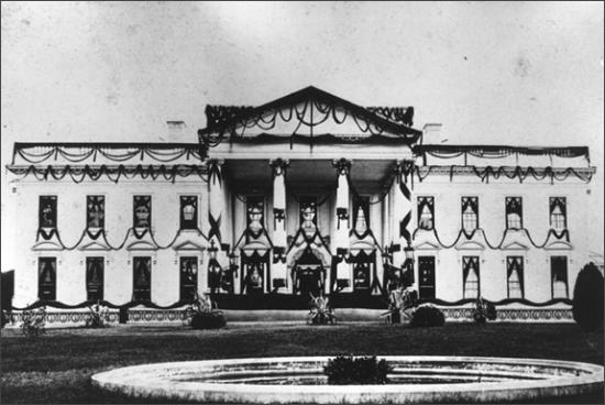 Black and white photo of white house with black decorations around windows and wreaths hanging on columns