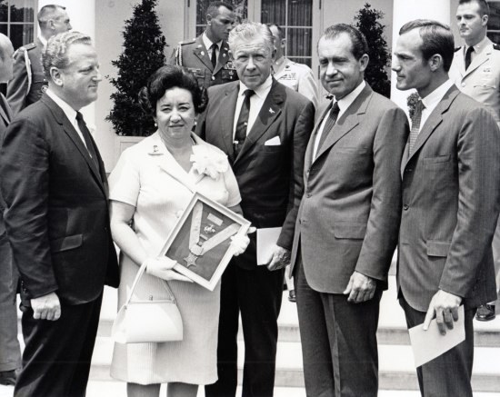 Black and white posed photo taken outside the White House. A woman holds a Medal of Honor in a frame. She wears white and stands beside a man in a suit. Around then, President Nixon and others.