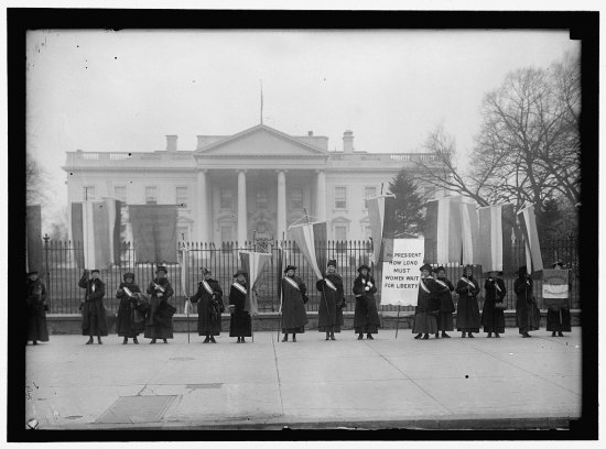 Black and white photo. In background, White House. In foreground, about 15 women in long dresses pose. Some hold up banners and signs.