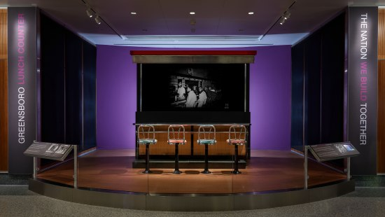 Photo of lunch counter on display in museum. Four chairs. Simple counter from a diner or deli. Behind counter, black and white photo of young men protesting.