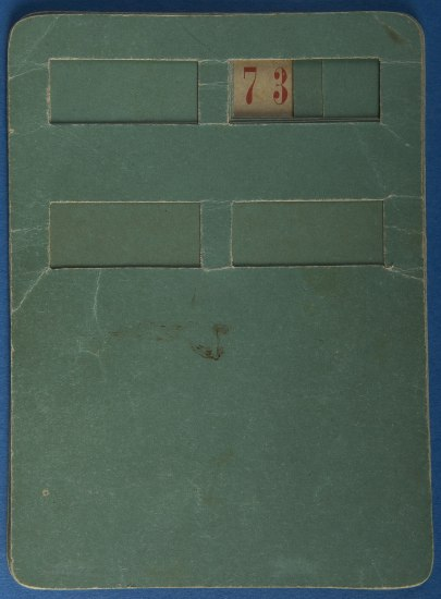 Green piece of paper with rectangular windows cut into the top piece of paper. One window reveals the number 73.