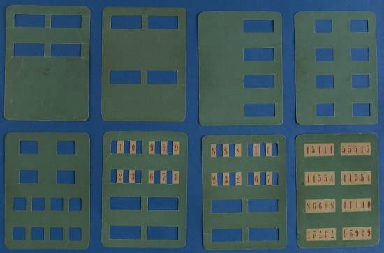 Many green sheets of rigid paper with rectangular windows cut into them, some revealing numbers.