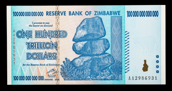 """One Hundred Trillion Dollars"" bank note from ""Reserve Bank of Zimbabwe."" It is blue, turquoise, and tan in color. The central image appears to be a mountain or rock outcropping made of three large stones. Palm trees and other vegetation appears tiny at its base. Geometric patterns are included in the bill, mostly triangles."