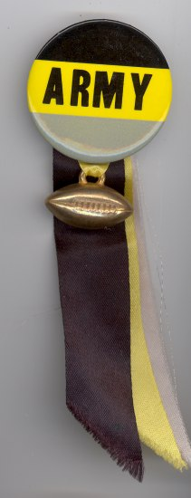 "A button with block, yellow and greay stripes saying ""ARMY."" A football charm is attached below and three ribbons hang from the back in gray, black and yellow."