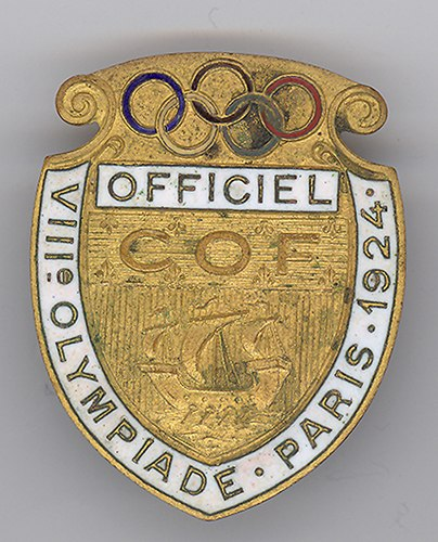 "A gold badge with the five Olympic rings at the top, a boat depcted in the middle, a white box that says ""Officiel"" on it and a similar white ribbon saying ""VIII Olympiade Paris 1924"""