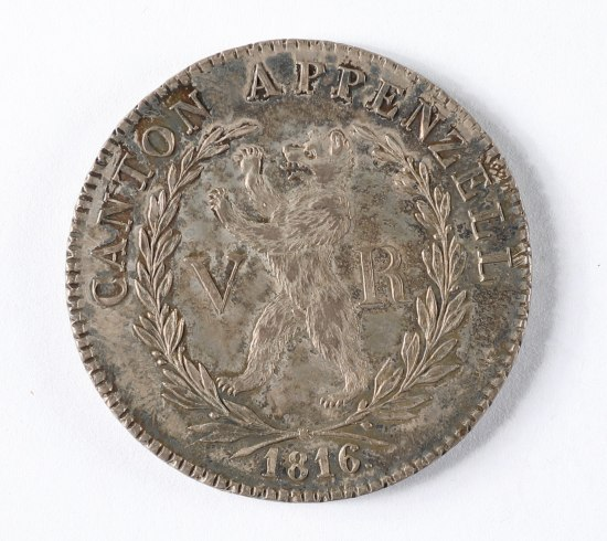 A silver-colored coin. A bear rears in the center within laurel leaves surrounded by text running around the edges.