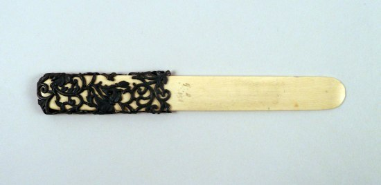 A beer comb which looks like a tongue depressor with an elaborate handle that is a black vine-like design