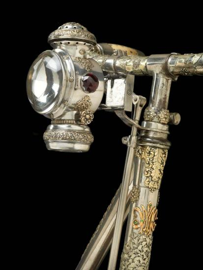 Detail of bicycle front with lamp and bejeweled monogram
