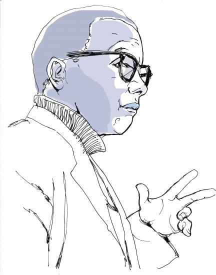 Side view of man with glasses, making an explanatory hand gesture