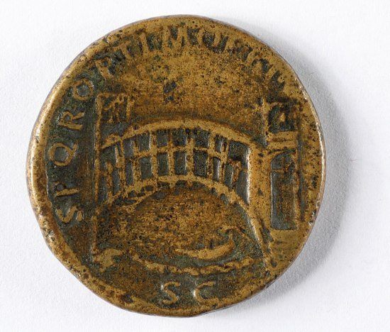 A bronze-colored coin. it features a bridge over a river with characters around the edges of the coin.