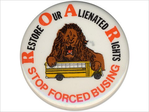 "White button features a drawing of a snarling male lion perched on top of small school bus. Around the button's border the text reads: ""Restore Our Alienated Rights...Stop Forced Busing."""