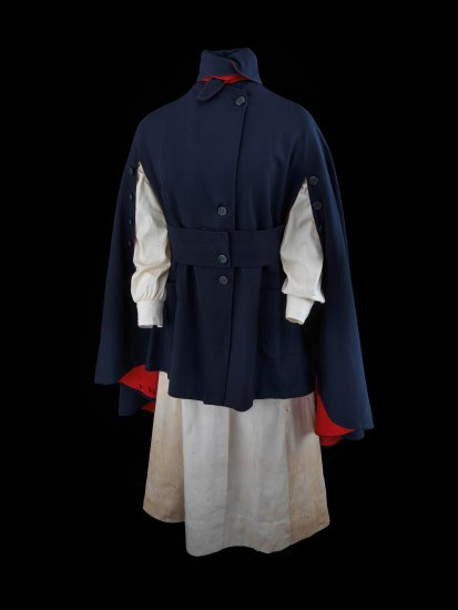 An outfit/uniform. There is a long-sleeved white dress underneath a navy cloak with buttons up the front. There are slits for the arms to poke out. The lining of the cape is bright red.