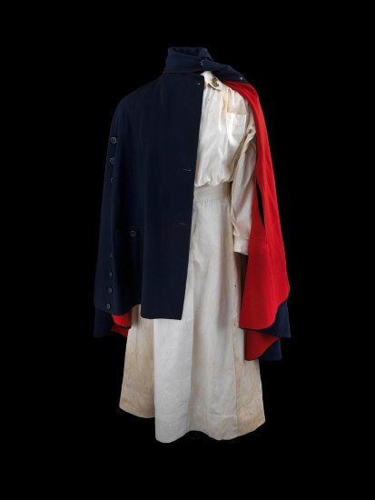 An outfit/uniform. There is a long-sleeved white dress underneath a navy cloak with buttons up the front. There are slits for the arms to poke out. The lining of the cape is bright red. The cape is pulled off slightly over the left shoulder so half or so of the white dress is visible.