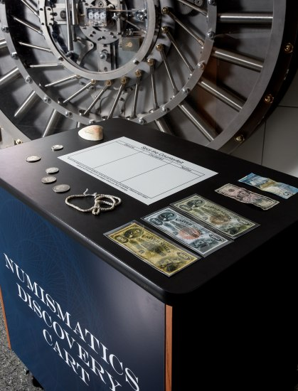 A somewhat aerial look at a small cart with paper currency, coins, a shell, some sort of string, and a piece of paper. There is a large vault door behind it.