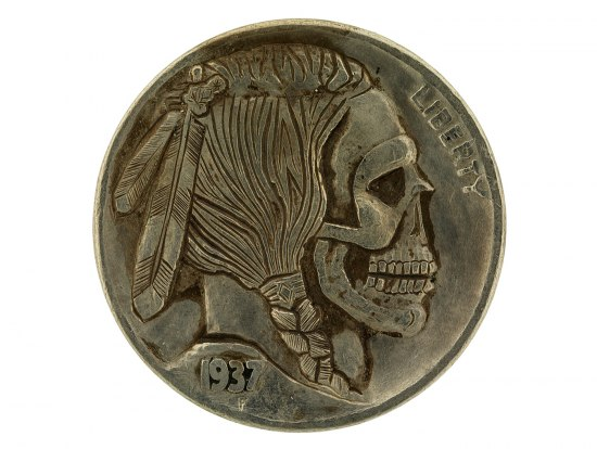 "A coin that looks to be made of some kind of bronze. On it, there is carved a skull with a Native American hairstyle and feathers. ""1937"" can barely be seen on the figure's shoulder."