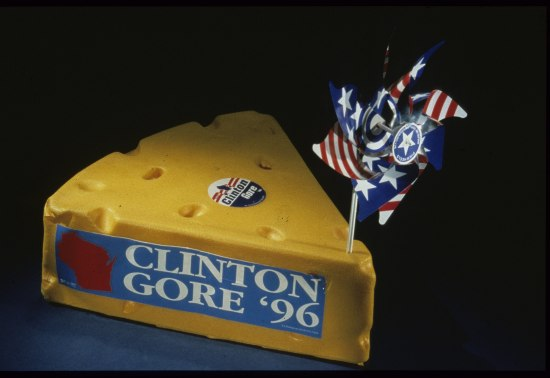 a hat that looks like a wedge of cheese adorned with bumper stickers and campaign stickers for Clinton Gore with a pinwheel stuck into the front