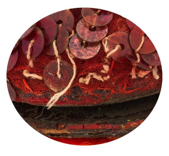 a magnified image of a sequined portion of one of the ruby red slippers. Threads have come loose, the sequins are dirty-looking and splotchy, ad the red fabric underneath is frayed. Also, it appears that the top part of the shoe is separating from the bottom.