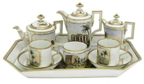 A group of porcelain items, including cups, kettles, saucers, and a tray. Everything is edged in gold and there are depictions of ruins on the items.