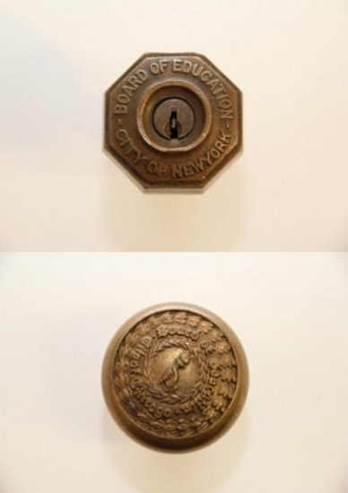 "Two photos of doorknobs. They are both brass-colored. The one on the top has eight sides and says ""Board of Education City of New York"" and has a keyhole in the middle. The bottom one is round with engraved laurel leaves, a hand holding a torch and ""Board of Education City of Chicago"" carved in."