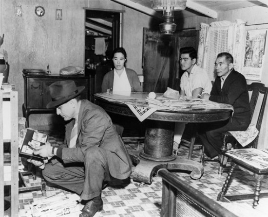 A black and white photograph of several people sitting at a table while a man in a suit with a hat on kneels in the forefront, reading something. There are letters on the ground in front of him.