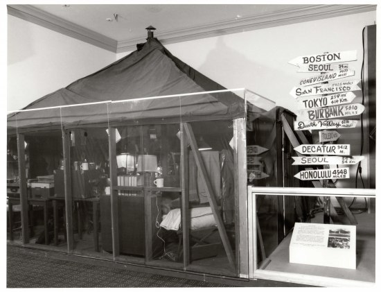 Prop tent with artifacts on display in the museum beside direction sign