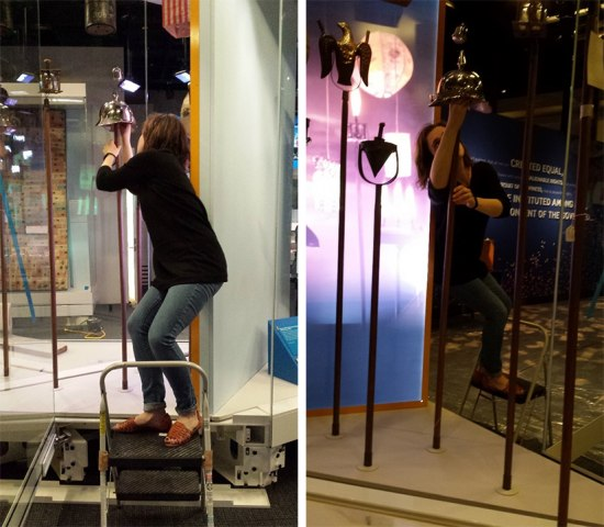 Two images. In both, a museum staff member stands on a step ladder, leaning to the side in order to adjust the placement of a campaign torch topper on a pole.